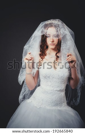 Beautiful Brunette Woman with sexy lips. Hairstyle. Makeup. Manicured nails. Fashion girl isolated on black background. Portrait of the beautiful bride on a dark background. - stock photo