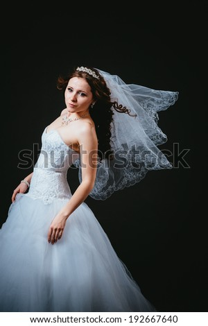 Beautiful Brunette Woman with sexy lips. Hairstyle. Makeup. Manicured nails. Fashion girl isolated on black background. Portrait of the beautiful bride on a dark background.