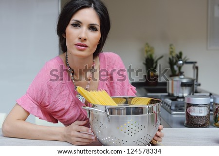 Beautiful brunette woman woman with a bowl of pasta cooking dinner in the kitchen - stock photo