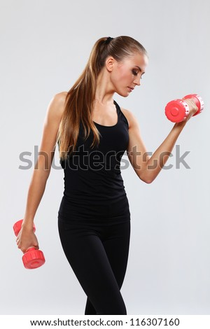 Beautiful brunette working out with dumbbells over gray background - stock photo
