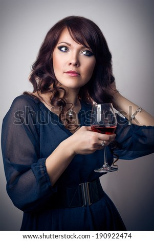 Beautiful brunette young girl holding a glass of wine  - stock photo