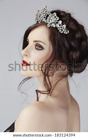 Beautiful brunette young model with braided hair with shiny crown in studio - stock photo