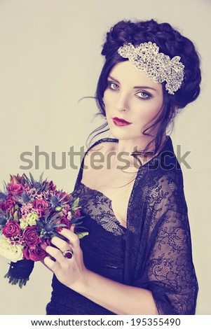 Beautiful brunette young model with braided hair with shiny crown wearing black lace dress in studio - stock photo