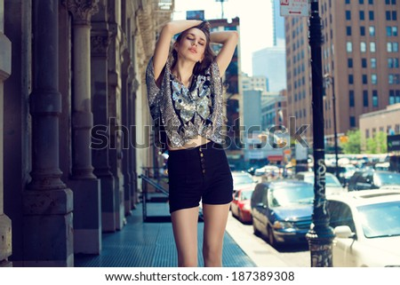 Beautiful brunette young woman in glitter top posing on the street  - stock photo