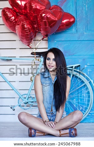 Beautiful brunette young woman in jeans  with a heart-shaped balloons near bicycle. Valentine's day. - stock photo