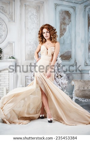 Beautiful brunette young woman in luxurious long dress in expensive interior - stock photo
