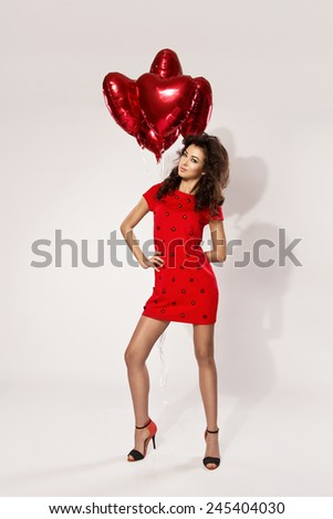 Beautiful brunette young woman in red dress with a heart-shaped balloons. Valentine's day - stock photo