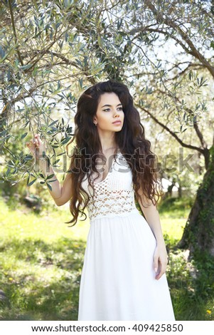 Beautiful brunette young woman outdoor portrait with long wavy hair in white dress. Attractive girl model posing in park.  - stock photo