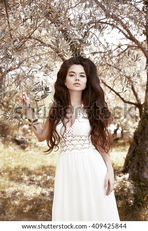Beautiful brunette young woman portrait. Attractive girl with long wavy hair in white dress posing on nature park background. - stock photo