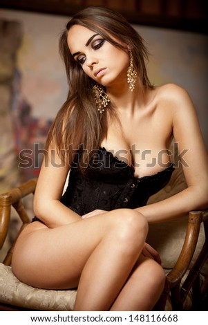 Beautiful brunette young woman sitting on rattan chair