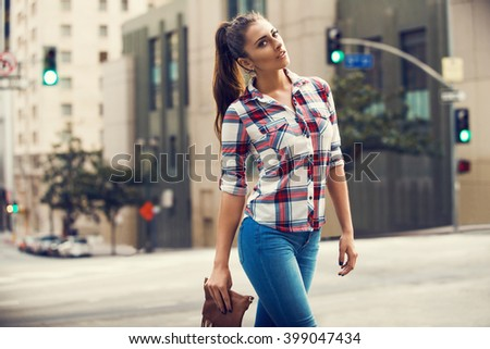 Beautiful brunette young woman wearing jeans and shirt, boho handbag and walking on the street