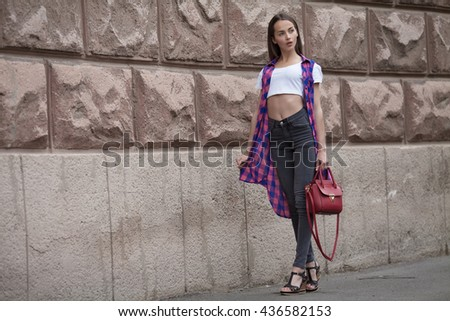 Beautiful brunette young woman wearing jeans and walking on the street . Red bag in woman hand. woman with long leg.