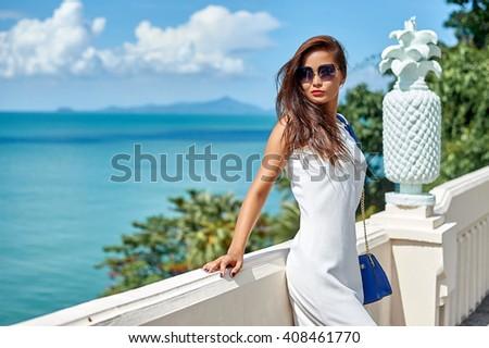 Beautiful brunette young woman wearing white dress and sunglasses