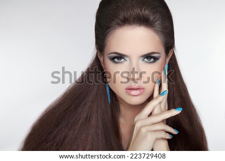 Beautiful Brunette young woman with fashion earring. Makeup.  Manicured nails. Studio photo. - stock photo