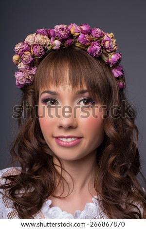 beautiful brunette young woman with wreath of flowers studio shot  - stock photo