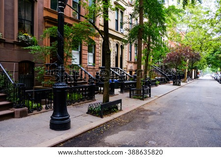 Beautiful buildings in Greenwich Village, Soho. Entrance doors with stairs and trees, Manhattan New York. Classic apartment building in New York City. - stock photo