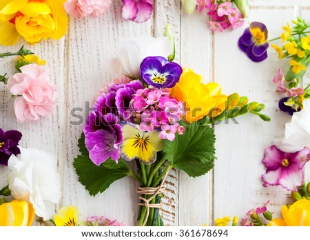 Beautiful bunch of flowers on the wooden table - stock photo