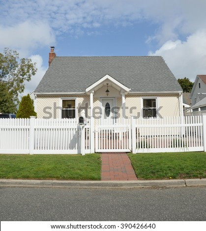 Beautiful Bungalow Home with white picket fence sunny blue sky clouds day residential neighborhood USA - stock photo
