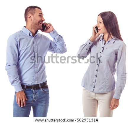 Beautiful business couple in smart casual wear is talking on the mobile phones, looking at each other and smiling, isolated on white