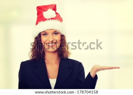 Beautiful business girl wearing santa's cap  - stock photo