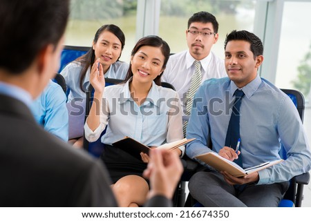 Beautiful business lady raising hand at the seminar - stock photo