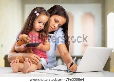 Beautiful business mom  in suit with kid is reading book
