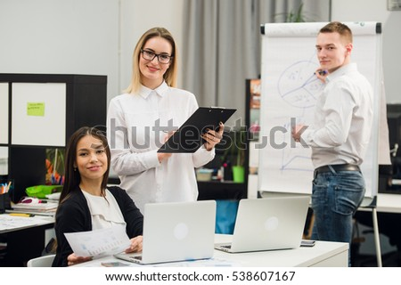 Beautiful business people are looking at camera and smiling while standing in office