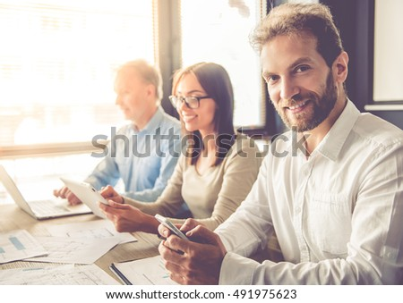 Beautiful business people are using gadgets while working in office. One businessman is looking at camera and smiling
