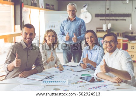 Beautiful business people in classic shirts are showing Ok signs, looking at camera and smiling while working in office
