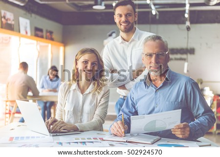 Beautiful business people in classic shirts are using a laptop, looking at camera and smiling while working in office