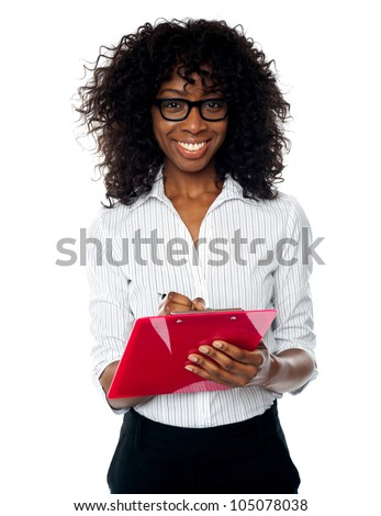 Beautiful business professional making notes. Wearing eyeglasses - stock photo