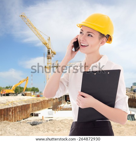 beautiful business woman architect in builder helmet talking by phone at construction site - stock photo
