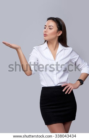 Beautiful business woman blowing on palm, looking at copy space on her palm, over grey background - stock photo