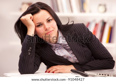 beautiful business woman bored at the work place - stock photo