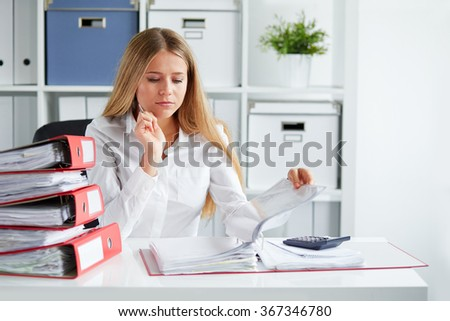 Beautiful business woman calculates tax at desk in office - stock photo