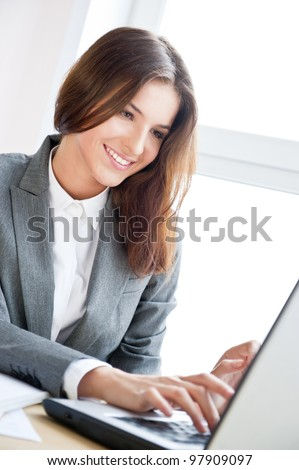 Beautiful business woman dreaming while working on computer at her office