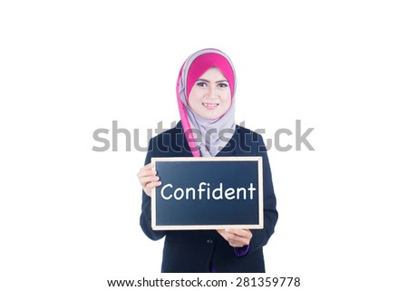 Beautiful business woman holding confident text on chalkboard with isolated over white background - stock photo