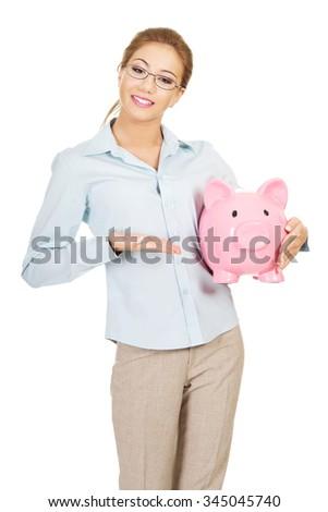 Beautiful business woman holding piggy bank. - stock photo