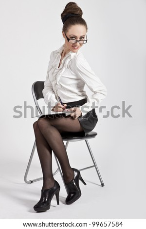 beautiful business woman in glasses is sitting in his chair, smiles and writes a pen on paper - stock photo