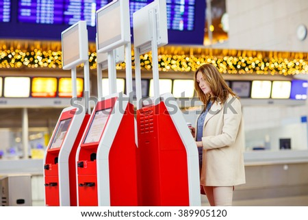 Beautiful business woman in international aiport. Ready to fly. Frankfurt airport, Germany. at international airport checking in on electronic terminal waiting for her flight. Upset passenger.  - stock photo