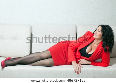 Beautiful business woman in red formal suit lies on a white couch