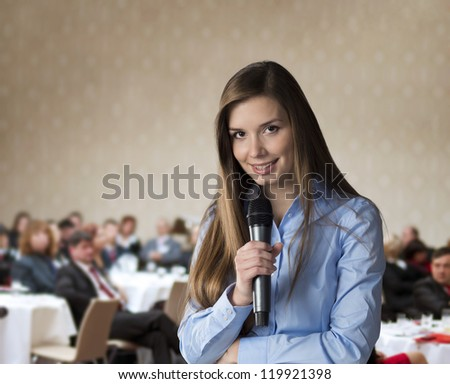 Beautiful business woman is speaking on conference.