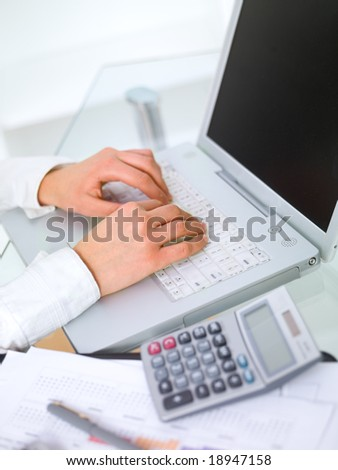 Beautiful business woman is working on laptop in office