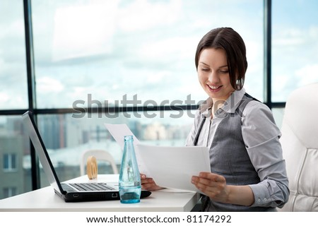Beautiful business woman looking at papers she holding in her arms while working on computer at her office - stock photo