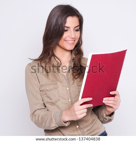Beautiful business woman looking at papers,she smiles.  on white background.