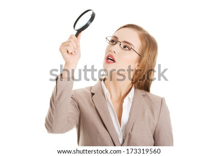 Beautiful business woman looking through magnifying glass. Isolated on white. - stock photo