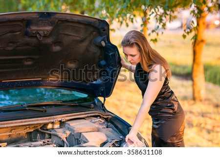 Beautiful business woman near her broken car, tring to repair
