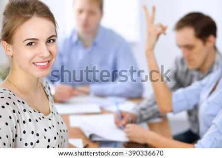 Beautiful business woman on the background of business people during meeting. Casual clothing style. Start up team. - stock photo