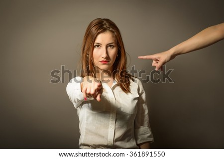 Beautiful business woman point finger at you looking at camera with someone else pointing on her, studio shot on gray background - stock photo