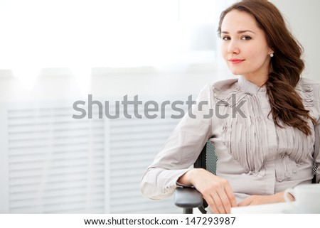 Beautiful business woman sitting at office, window outside background